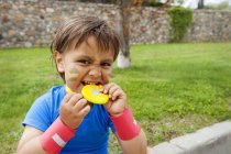 Little boy biting on medal — Stock Photo
