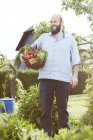 Young man standing in garden, basket with fresh vegetables — Stock Photo