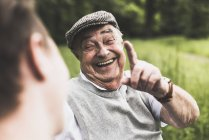 Portrait of laughing senior man talking to his grandson — Stock Photo
