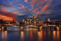 View to skyline with Ignatz-Bubis-Bridge and Main River in the foreground by sunset, Frankfurt, Germany — Stock Photo