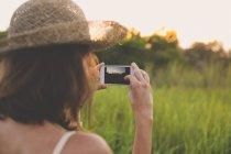 Vue arrière de la femme prenant des photos avec smartphone dans la nature — Photo de stock