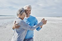Happy couple dancing on the beach — Stock Photo