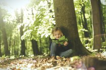 Girl in forest examining leaves — Stock Photo