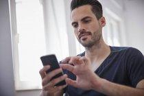 Homem adulto médio usando telefone inteligente — Fotografia de Stock
