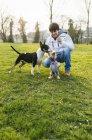 Jeune homme jouant avec des chiens sur la prairie verte — Photo de stock