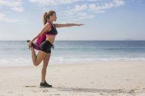 Deportiva mujer haciendo ejercicio en la playa - foto de stock