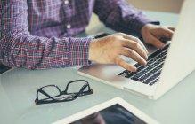Hombre usando el ordenador portátil en el escritorio, vista parcial - foto de stock