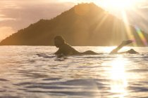 L'Indonésie, l'île de Sumbawa, surfeur femelle allongé sur la planche de surf dans la soirée — Photo de stock