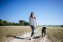 Junge Frau, die ihren Hund in ländlichen Landschaft spazieren gehen — Stockfoto