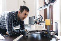 Worker controlling model on 3D printer at daytime — Stock Photo