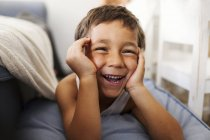 Portrait of laughing little boy with head in his hands — Stock Photo