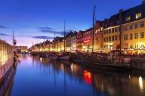 Dänemark, Kopenhagen, Blick auf historische Boote und Häuserzeile am Nyhavn am Abend — Stockfoto