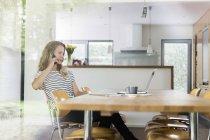 Frau am Handy sitzt am Tisch — Stockfoto