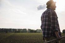Farmer holding rake next to a field — Stock Photo