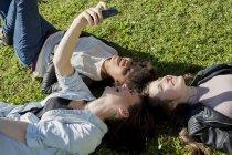 Três amigas deitadas na grama tirando selfie com telefone inteligente, vista elevada — Fotografia de Stock