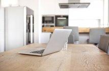 Ordenador portátil en una mesa de madera en una cocina abierta - foto de stock