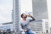 Молодой человек сидел на стене, пить кофе — стоковое фото