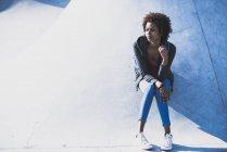 Mujer joven sentada pensando al aire libre - foto de stock