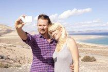 Испания, Фуэртевентура, Хандия, пара принимая selfie на побережье — стоковое фото