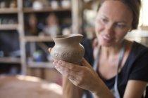 Lächelnd Potter in Werkstatt Blick auf Steingut Krug — Stockfoto