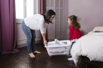 Mother and little daughter carrying  laundry basket together — Stock Photo