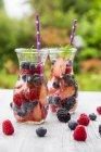 Дві скляні пляшки detox води, настояний з різних ягоди — стокове фото
