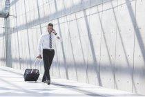 Бізнесмен з багажем і стільниковий телефон — стокове фото