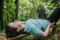 Young woman relaxing on bench in forest — Stock Photo