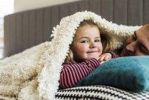 Pai e filha abraçando sob cobertor em casa — Fotografia de Stock