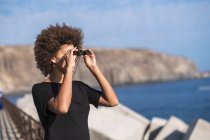 Spain, Tenerife, young woman on a jetty looking at distance with binocular — Stock Photo