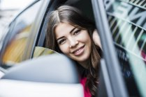 Brunette woman sitting in car looking through window — Stock Photo
