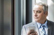 Senior homme caucasien tenant le téléphone cellulaire — Photo de stock
