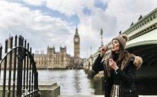 Regno Unito, Londra, giovane donna che soffia bolle di sapone davanti al Palazzo di Westminster — Foto stock