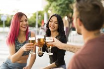 Friends in a bar toasting with beer glasses — Stock Photo