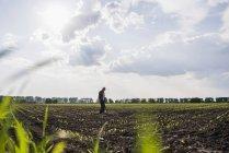 Agricultor de pé em um campo — Fotografia de Stock