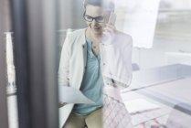 Mujer de negocios en el documento de lectura de teléfonos celulares - foto de stock