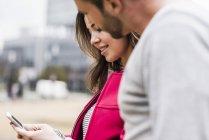 Giovane coppia controllare i messaggi di testo in città — Foto stock
