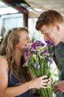Крупным планом Человек дарит цветы счастливой девушке — стоковое фото