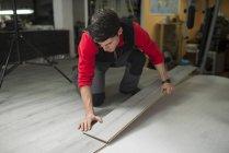 Young man placing a laminate floor — Stock Photo
