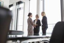Drei Geschäftsfrauen diskutieren am Fenster in modernem Büro — Stockfoto