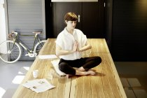 Woman practicing yoga on wooden table — Stock Photo