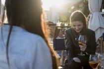 Young women sitting in bar drinking aperitif — Stock Photo