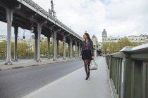 France, Paris, young woman walking on bridge — Stock Photo