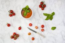 Tomato soup with tomatoes and knife on marble — Stock Photo