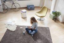 Жінка на дому, сидячи на підлозі, використовуючи цифровий планшетний — стокове фото