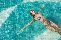 Woman floating on water of a swimming pool — Stock Photo