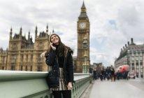 UK, Londra, felice giovane donna che telefona con lo smartphone di fronte al Palazzo di Westminster — Foto stock