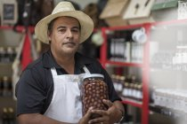 Shopkeeper in shop holding a jar with olives — Stock Photo