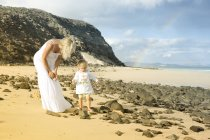 Mother and daughter relaxing together on beach — Stock Photo