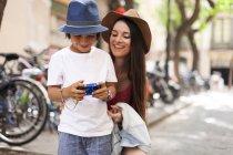 Madre e hijo tomando fotos en la ciudad - foto de stock